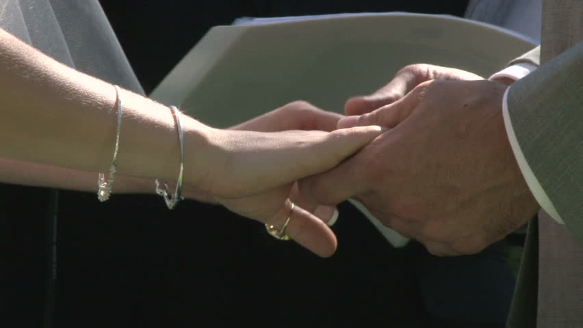 Bride and Groom holding hands on their wedding day during ceremony.