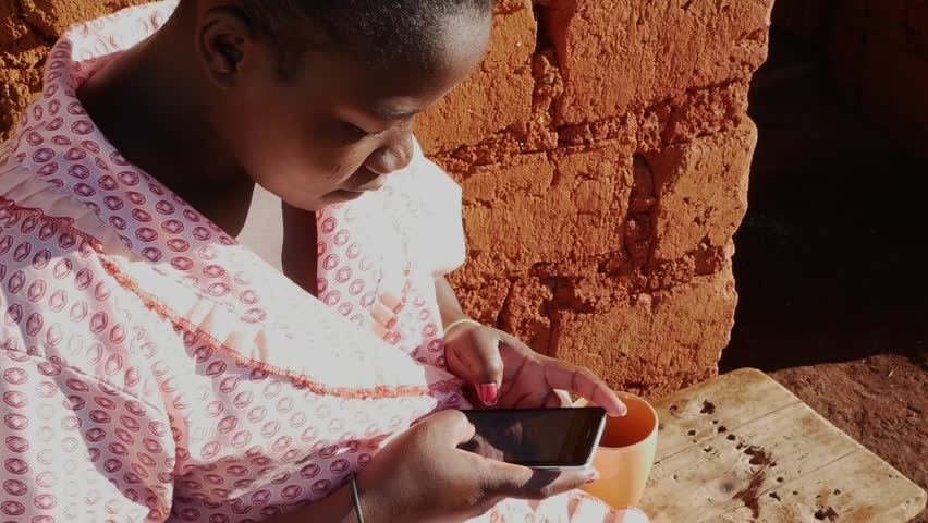 A South African black rural woman sitting down scrolling through her messages on her cell phone mobile telephone. | Shutterstock HD Video #27746398