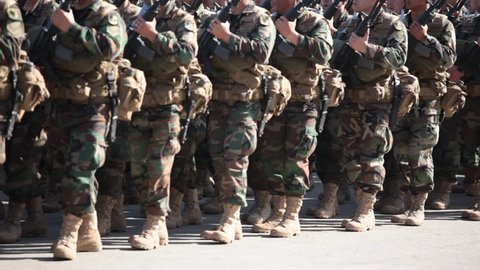 Soldiers marching on a paved road.