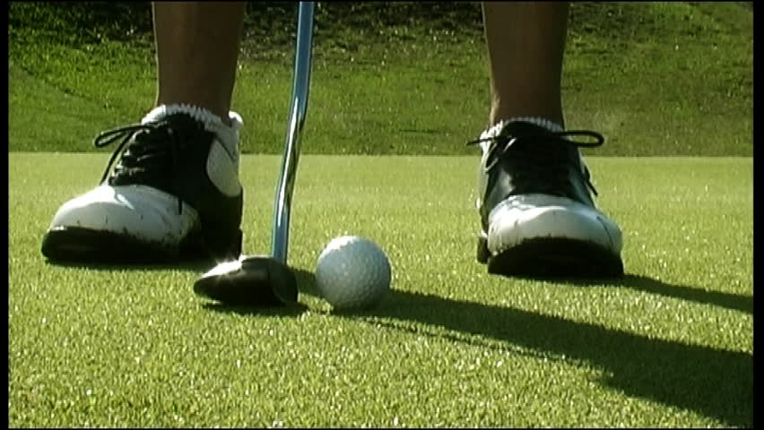 Low level close up of a pair of golf shoes on a golf course