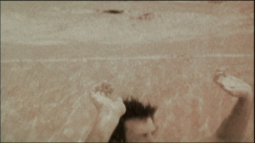 Young man leaping up through surface, water distorting image on camera, black and white image