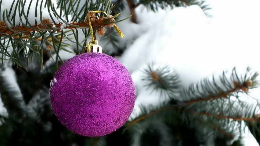 beautiful bright pink ornament  vibrant on the Christmas tree covered with snow