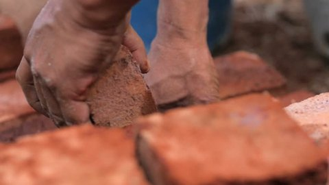 Strong man's hands building a house