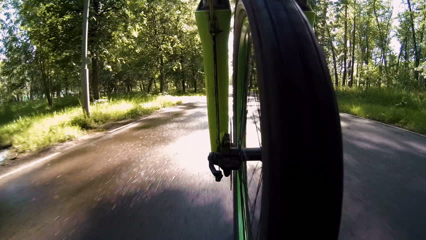 Close-up of Bicycle riding along the path in the Park. View from front wheel | Shutterstock HD Video #27801772