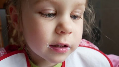 Little Beautiful Blonde Girl with Blond Hair and Blue Eyes Eats Spoon Yogurt or Cottage Cheese Curd