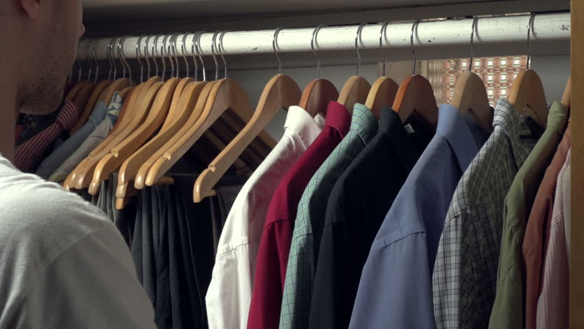 Man picking out a shirt to wear from his closet
