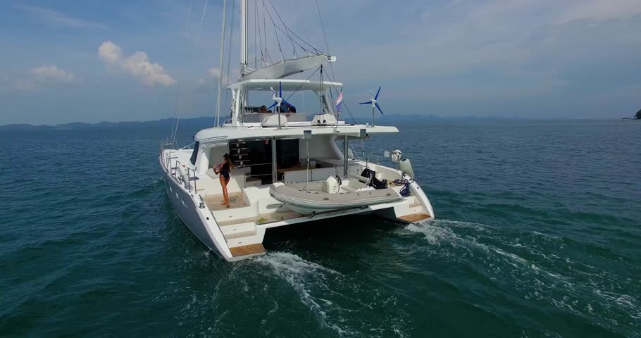 Aerial: Beautiful luxury yaht with pretty model sailing in Andaman sea. Dancing and relax on the boat. Phuket. Thailand.