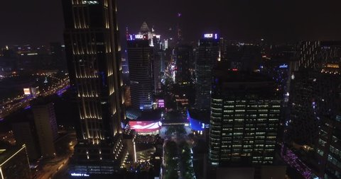 SHANGHAI MAY 2017: Flying downtown through buildings on huaihai middle rd. Shanghai China cityscape drone flying at night, with city lights and traffic on streets. Night time flying cityscape shot.
