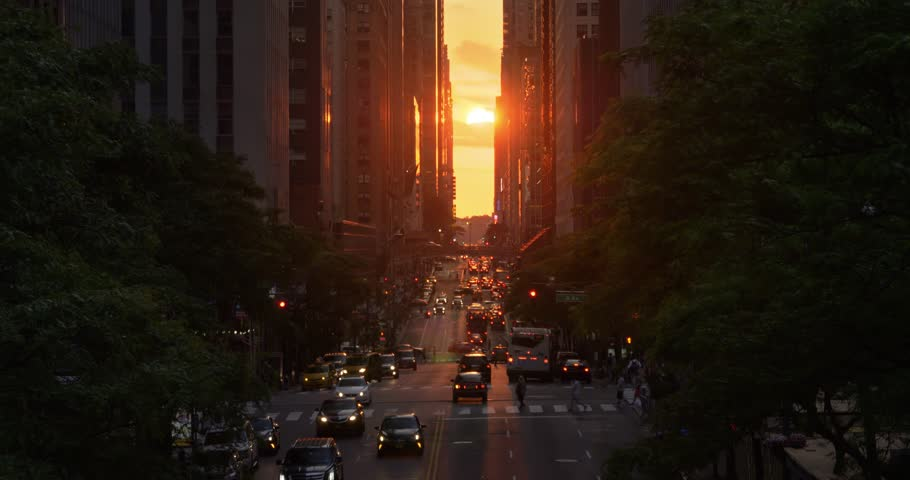 "A dramatic wide evening long establishing shot over 42nd Street in New York City during the ""Manhattanhenge"" solar event."