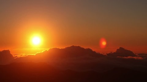 Red sun disk time lapse dawn with flowing cloud waves HDR, shot at Haleakala National Park, Hawaii