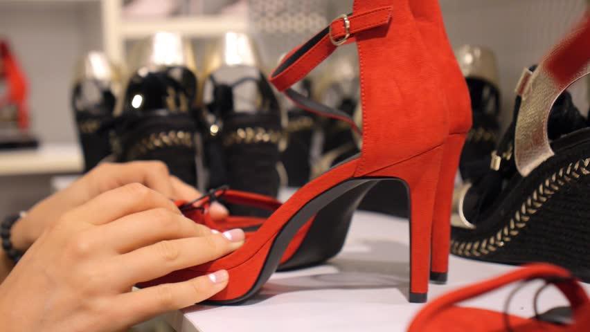 Woman Customer Choosing Red High Heels In Shoe Shop. Closeup. HD, 1920x1080.