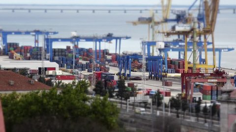 Huge Container Terminal Tilt Shift Time Lapse. A container terminal is a facility where cargo containers are transshipped between different transport vehicles