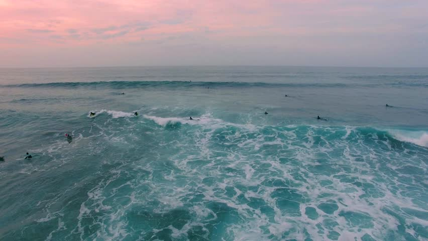 Aerial top down shot of textured ocean then reveals surfers in the sunset