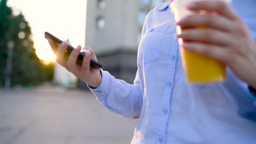 Woman talking on smartphone and drinking juice on the street | Shutterstock HD Video #27908908