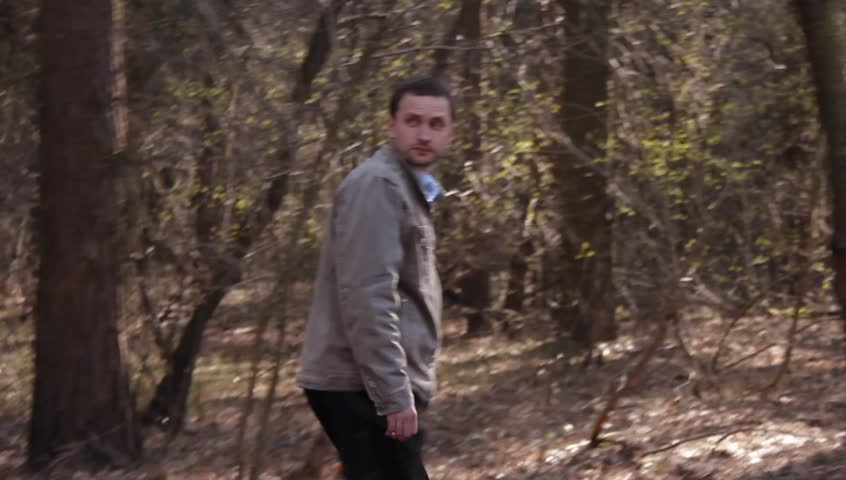 Ungraded: Bearded man walks wildly through the forest with bushes and thickets, looking around with caution. Source: Canon 60D, ungraded H.264 from camera without re-encoding. (av37042u)