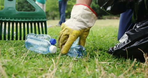 Close-up of volunteer collecting litter in park