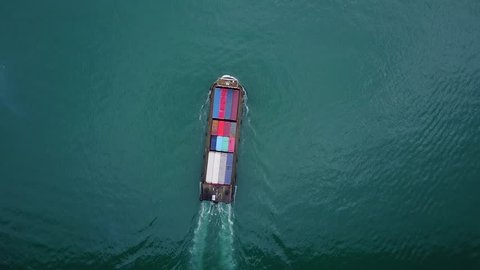 Small feeder container vessel aerial tracking shot from above. Ship sail through dark turquoise waters of Rambler Channel, approaching Tsuen Wan. Vessel loaded with standard steel containers