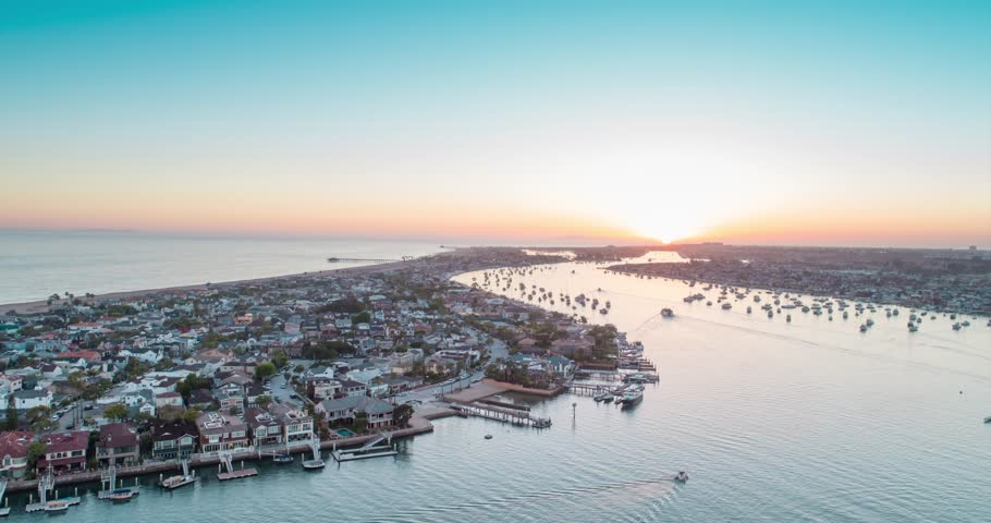 Newport Beach aerial sunset filmed with the drone over Balboa Peninsula with Newport harbor, boats, beach houses, Newport pier and the Pacific ocean in view.