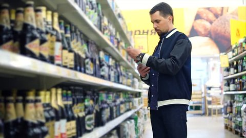 Man customer taking a bottle of beer from the shelf in the supermarket. Shopping in the section of alcoholic drinks