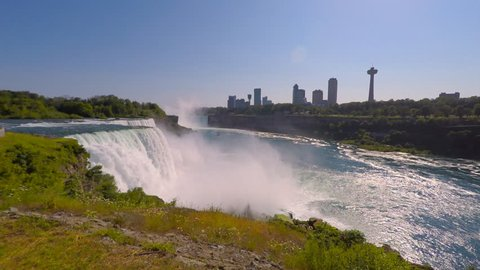 Niagara Falls State Park in New York, waterfalls roaring with mist, tour boats Hornblower and Maid of the Mist cruising on Niagara River. Skyline of Niagara Falls City on Canadian side in background