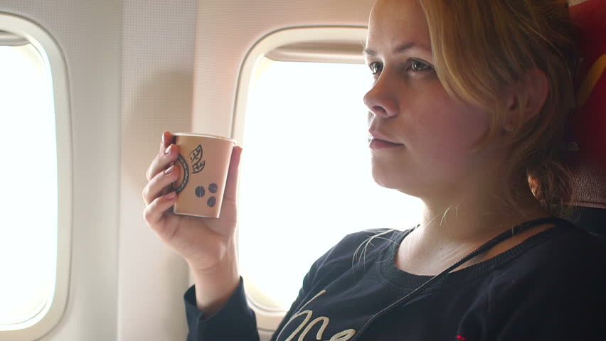 Beautiful tired woman drinking coffee on the plane, close-up. Slow motion. | Shutterstock HD Video #28006048