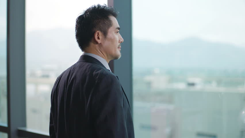 Businessman standing in front of windows looking into distance