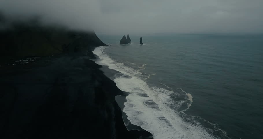 Aerial view of the black volcanic beach in Iceland and troll toes rocks in the sea. Copter flying over wave with foam.