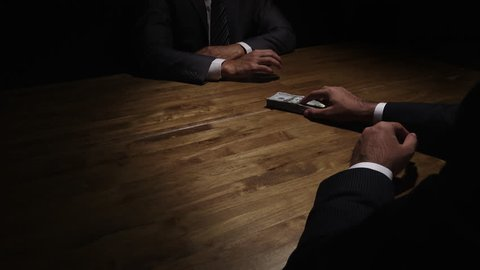 Businessman giving money to his partner on the table in the dark - bribery and corruption concepts