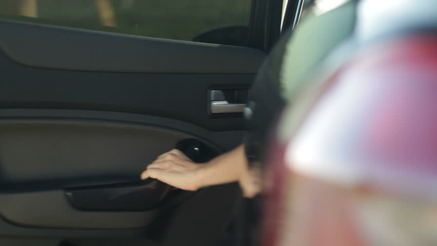 Close-up on a woman getting out of car