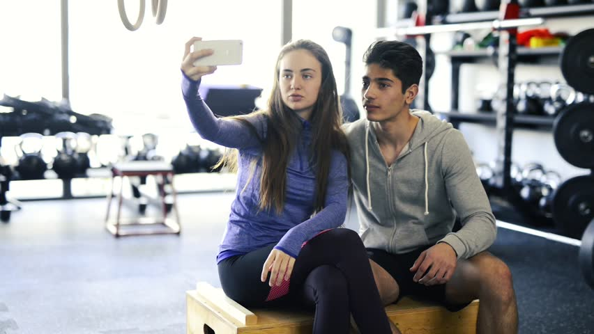 Fit couple in crossfit gym taking selfie with smartphone. | Shutterstock HD Video #28075243