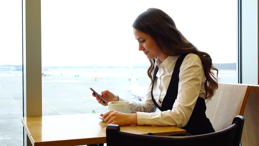 Young adult woman sit by small table against window in cosy cafe at airport  lounge, browse smartphone and drink coffee. Turn head and look straight to  ...