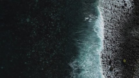 Aerial view of ocean waves clashing on rocky coastline on Madeira (Portugal) by drone