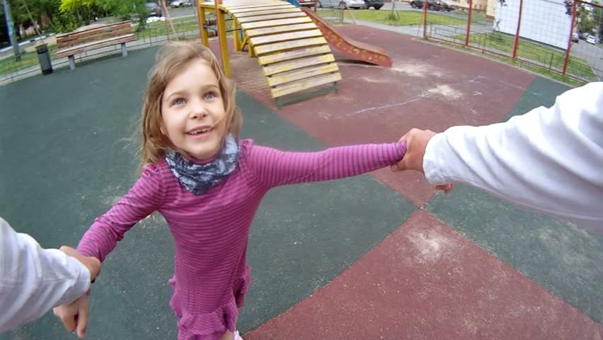 Father twist the daughter by hands at playground in house yard