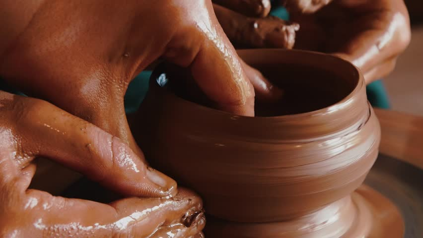 Creating a clay pot.Potter.A turner.Workshop of clay.Clay on the device.Master.Hands working on pottery wheel, shaping a clay pot