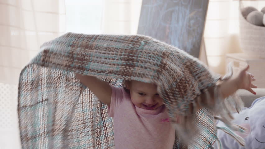 Little child kid is very happy and laughing with bright fantasy while playing game hide and seek under the blanket on the sofa at home