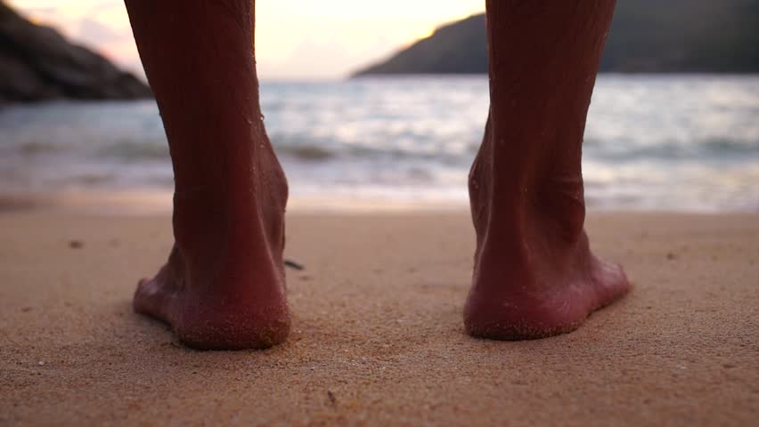 Feet of a young man walking towards the sea at sunset. Out of focus