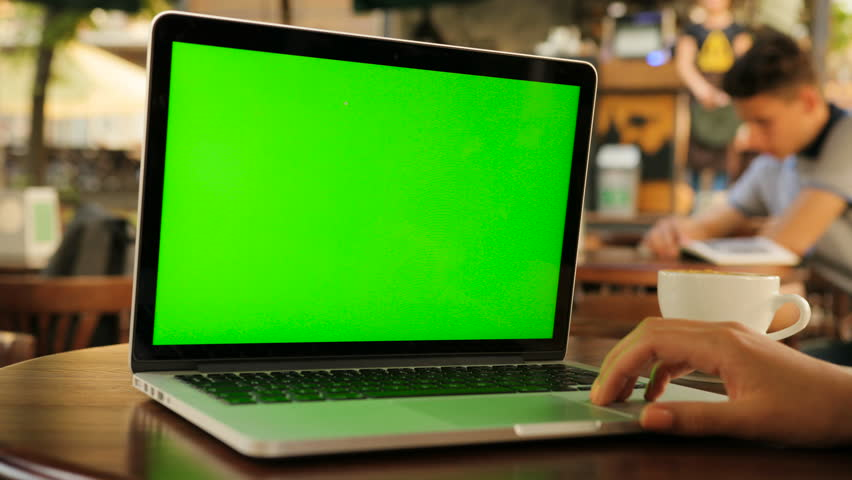 Woman using laptop computer with green screen while sitting outside in the cafe. Female hands typing on laptop keyboard. Close up. Chroma key.