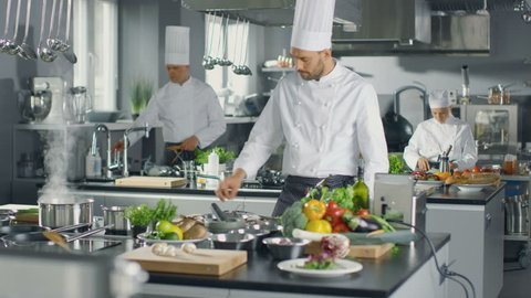 Famous Chef and His Staff Working in a Big Restaurant Kitchen. Place Has Clean Modern Design. Shot on RED EPIC-W 8K Helium Cinema Camera.