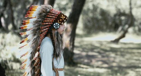 4K CINEMAGRAPH - seamless loop. Little girl playing in a teepee tent outdoors, wearing Indian headdress, pretending to be a native American