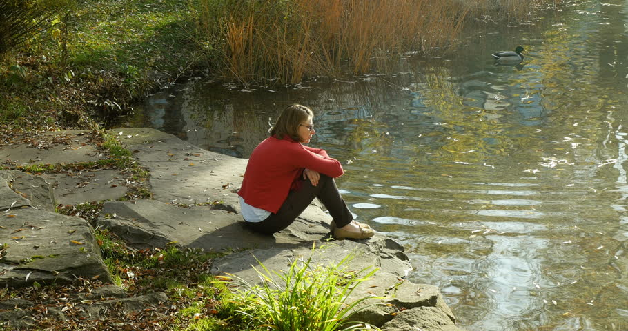 Pensive young Caucasian woman admiring the lake and the mallard duck on a warm autumn day   Shutterstock HD Video #28243798