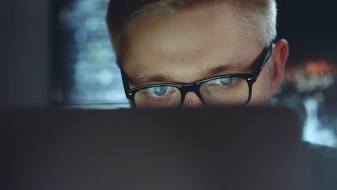 Businessman working late at night looking at monitor, reflections in glasses, male stock market trader using laptop at office