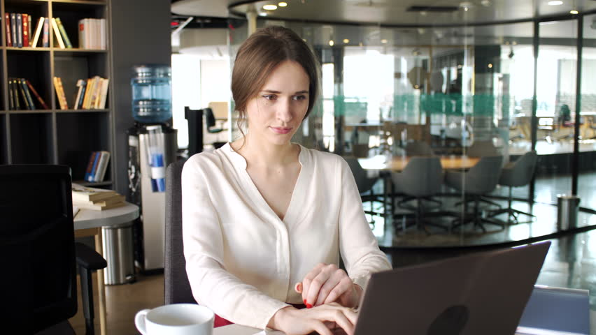 Busy beautiful young woman work on laptop computer with business papers, pick up telephone work call sitting at the table in office space during sunny day alone | Shutterstock HD Video #28296688