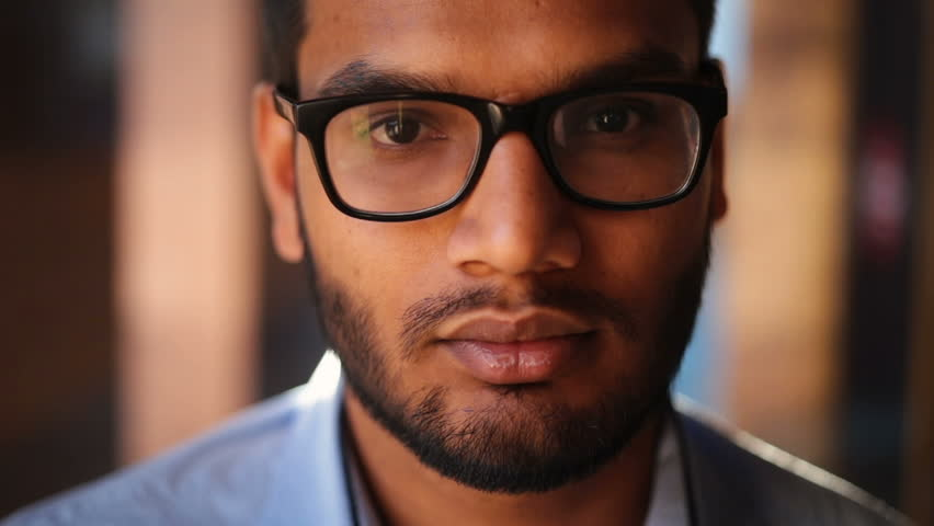 Portrait of a young African American in glasses looking into a camera, serious | Shutterstock HD Video #28305298