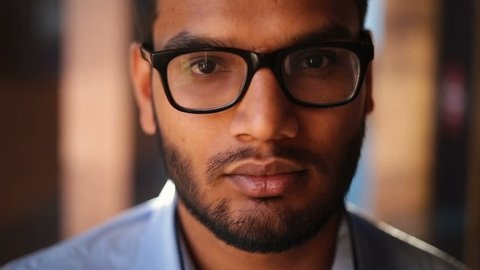 Portrait of a young African American in glasses looking into a camera, serious