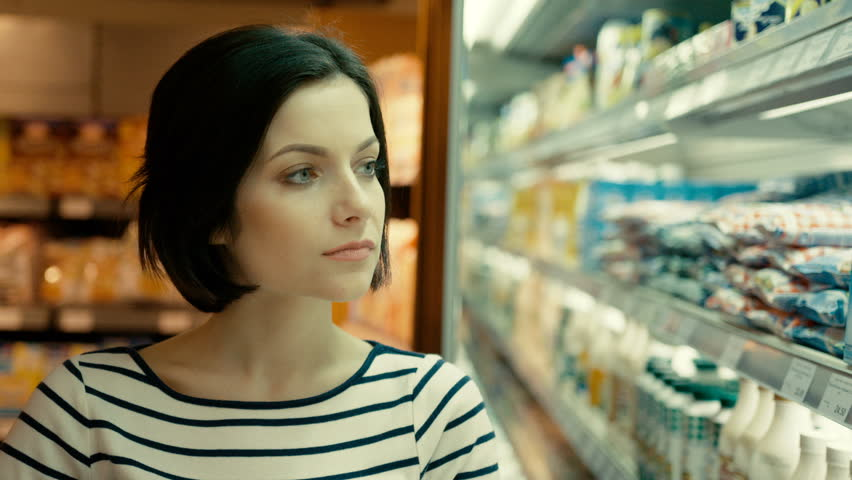 Portrait of attractive woman trying to choose the dairy products in the supermarket.