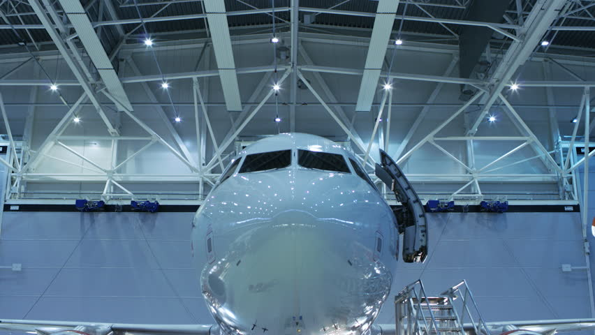 Up-Down Shot of a Brand New Airplane Standing in a Aircraft Maintenance Hangar while Aircraft Maintenance Engineer/ Technician/ Mechanic Visually Inspects Plane with a Flashlight.Shot on RED 8K Camera | Shutterstock HD Video #28318018