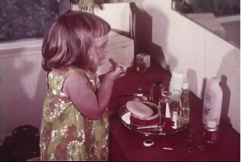 1960s: A mother catches her little girl in the act of putting on the mom's makeup, and takes her away to keep her safe from potential hazards, in a scene from a 1960s film about poison safety.