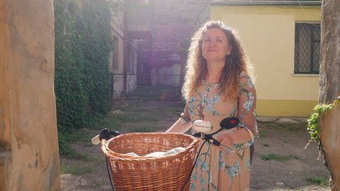 Portrait of young smiling woman with curly red hair standing with vintage bike in old european courtyard. Slow motion.