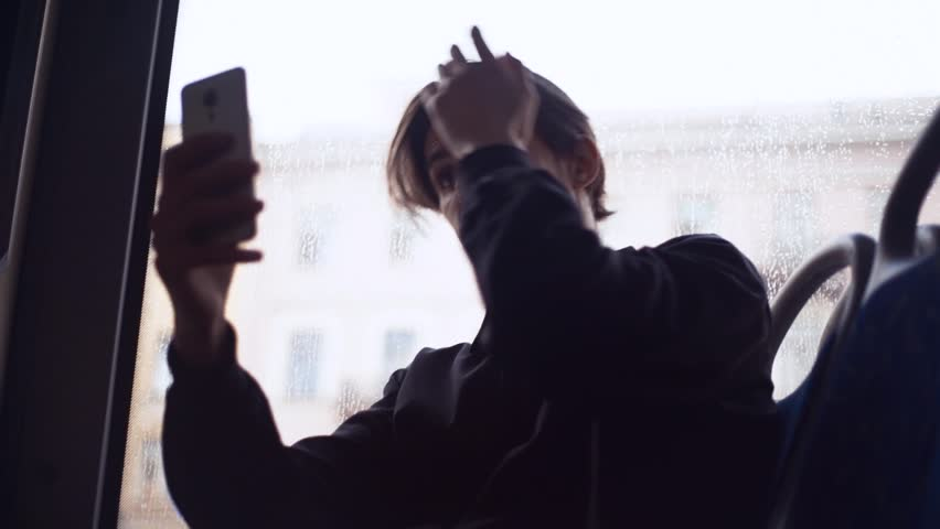 Caucasian young man in dark clothes correcting hairstyle looking at the camera smartphone during bus ride. Rain outside the window | Shutterstock HD Video #28330588