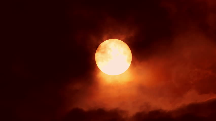 Big sun disk in sunset in cloudy sky timelapse. horror and terror background. ecology and pollution concept. Red moon. Wolf Night background. red smoky sky with a big red sun.